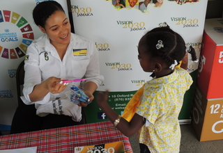 Picture showing a staff member of Vision 2030 Jamaica handing a pink pen to a little girl at the UNFPA World Population Day 2017 Commemoration Ceremony that was held in Santa Cruz, St. Elizabeth on July 11, 2017