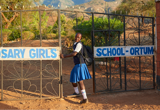 """Sharleen, aged 17, enters the school where she continues her studies in Kenya. Her teachers supported her to resist mutilation and early marriage. """"My family wanted me to be cut and get married, but I refused,"""" she said.  """"I have stayed firm in pursuing my education."""" Photo by Luca Zordan for UNFPA."""