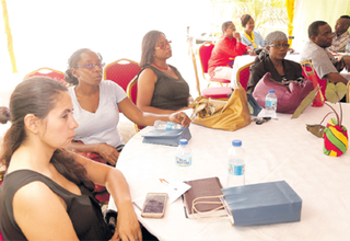 Guests listen attentively during the launch and open day of Groots on Friday at Niles Street, Tunapuna. PHOTOS: ABRAHAM DIAZ